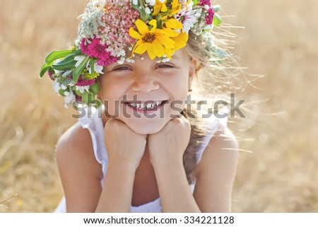 Stock Photo Two adorable little sisters wearing flowers crowns by warm and sunny summer day
