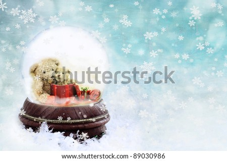 Two adorable little teddies inside of a Christmas snow globe against a blue background. Shallow depth of field with selective focus on snowglobe.