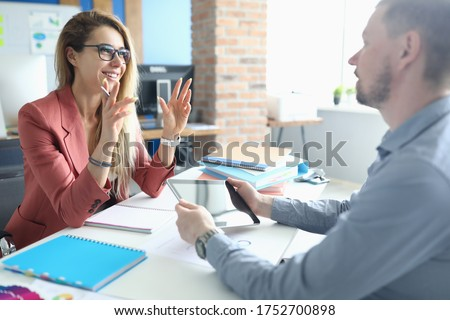 Photo of  Two adult business people make work interview against office background.One on one meeting concept.