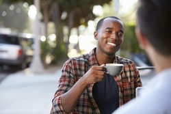 Two adult male friends sit talking over coffee outside cafe