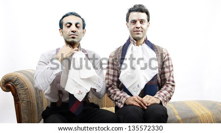 Two adult man wearing old-man clothes and makeup. One is adjusting a cloth napkin on his neck while the one on the right sits looking at the camera. Isolated on white background.