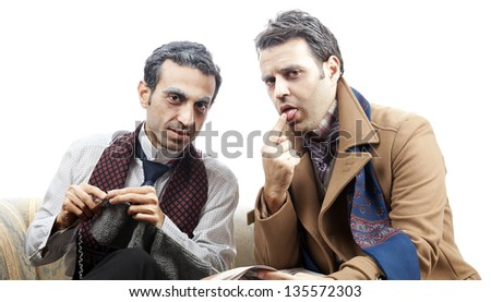 Two adult man wearing old-man clothes and makeup. One of them is knitting while the other wetting his finger with his tongue in order to flip the page of the newspaper. Isolated on white background.
