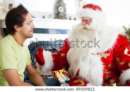 Two adult men - old father wearing Santa Claus suit and his adult middle aged son talking in front of fireplace at home