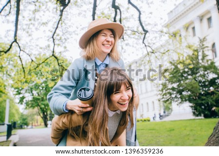 Two adult playfull good looking women sisters in trendy coat piggybacking her pretty girlfriend in spring park outdoor. Real emotion, true friendship female concept. #1396359236