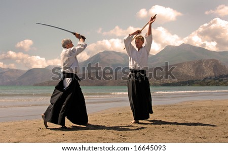 two adults are training in aikido on a beach in japon