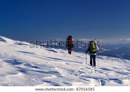 Two adventurers are on the snow slope