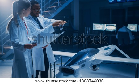 Two Aerospace Engineers Work On Unmanned Aerial Vehicle / Drone Prototype. Aviation Scientists Talking, using Blueprints. Industrial Laboratory with Commercial Aerial Surveillance Aircraft ストックフォト ©