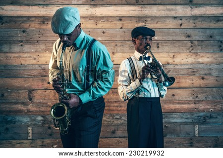 Two african american jazz musicians playing trumpet and saxophone. Standing in front of old wooden wall.