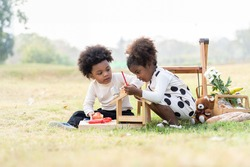 Two African American little boy and girl playing toy together in the park. Children with curly hair having fun together outdoor. Black kid people enjoying outside