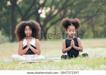 Two African American little girl doing meditate yoga asana on roll mat with eyes closed in park. Kids girl practicing doing yoga outdoor. Little afro girl with curly hairstyle training yoga together