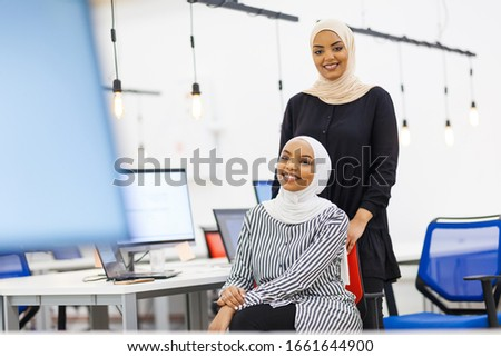 Two african american muslim girl colleagues with hijab posing together in a modern office. Monitors and light bulbs in the background and foreground