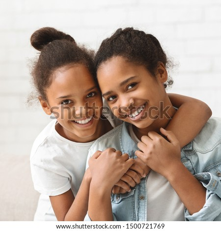 Two african beautiful sisters hugging each other, white background ストックフォト ©