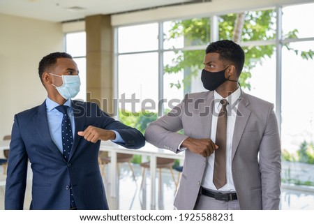 Two African businessman wearing medical mask while greeting with elbow bump greeting at office. Social distance concept during the coronavirus epidemic. Zdjęcia stock ©
