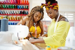 Two african dressmaker woman sews clothes on sewing machine and work with scissors at tailor office. Black seamstress girls.