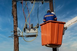 Two African electrician on the orange basket of a crane on the pole