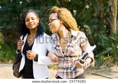 two african female college students walking to school classroom