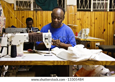 Two african man sewing in a small tailor shop, industrial sewing machine, African small industry