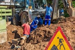 Two African repairman attending to the city water supply repairs in Gaborone Botswana