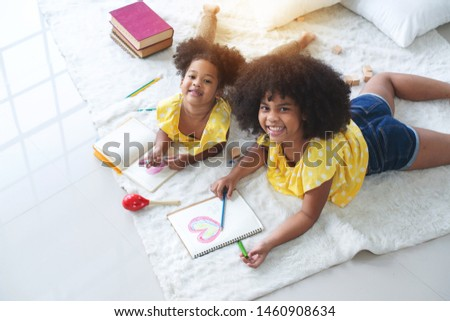 Two African sisters are lying on the floor and drawing a big heart for mothers, top view