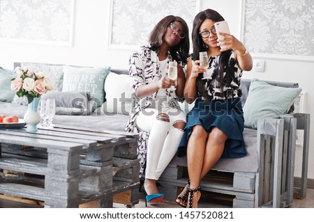 Two african woman friends wear on eyeglasses posed indoor white room, drinking champagne and making selfie.