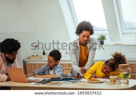 Two afro children and their parents doing homework together while sitting at the table Photo stock ©