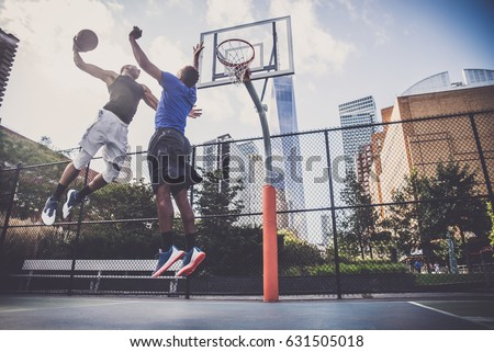 Two afroamerican athletes playing basketball outdoors - Basketball athlete training on court in New York