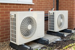 Two air source heat pumps installed on the exterior of a modern house