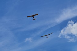 two aircraft flying in the blue sky.