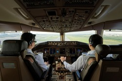 Two airliner pilots are flying the airplane towards the runway. Outside cockpit can see landing runway and airport. Inside cockpit can see pilots and all flight instrument and equipment.