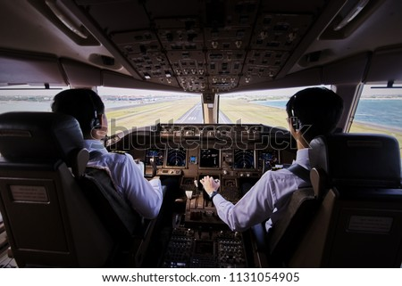 Two airliner pilots are flying the airplane towards the runway. Outside cockpit can see landing runway and environment. Inside cockpit can see pilots and all flight instrument and equipment.