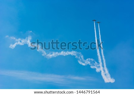 Two Airplanes Executing a Spectacular Ascent in a Long Trail on the Blue Sky #1446791564