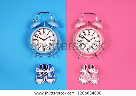 5cbe569e4ca9c4 Two alarm clocks on blue pink background, boy or girl concept #1206854008