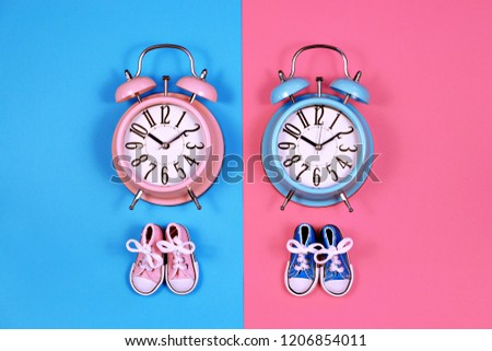 19f36e20bcde7e Two alarm clocks on blue pink background, boy or girl concept #1206854011