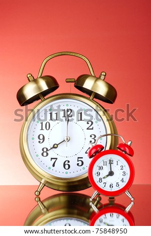 Two Alarm-clocks on red background