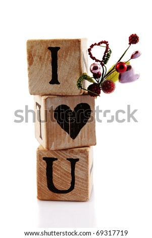"Two alphabet blocks and one with a heart stacked to read, ""I Love You.""  Isolated on white."
