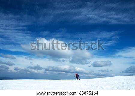 two alpine skiers under dramatic sky