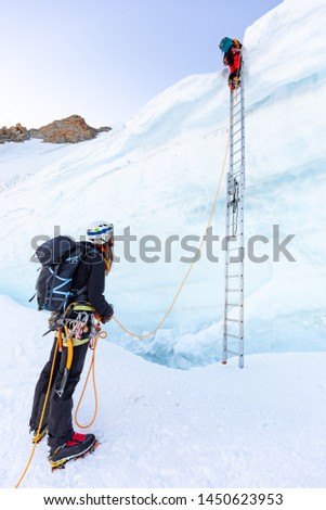 Two alpinists mountaineers ascent ladder over ice snow crevasse crack, extreme sport  mountain climbing. Mont Blanc massif, Europe travel tourism. #1450623953