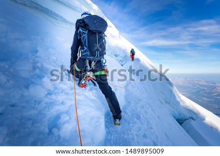 Two alpinists mountaineers climbing ascending over ice snow crevasse crack, extreme sport  mountain climbing. Mont Blanc massif, Europe travel tourism.