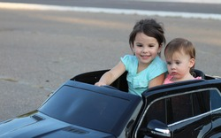 Two amazing girls ride in one big toy car on city street asphalt. Outdoor driving in a summer attraction for children