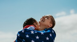 Two american female athletes wrapped in national flag giving a hug to another after winning the competition. Excited sportswomen embracing each other after a victory.