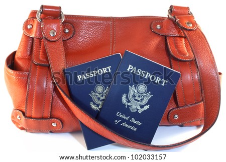 Two American passports with orange leather travel purse isolated on white background.