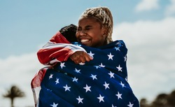 Two american woman athletes giving a hug to another after winning the competition. Excited female athletes embracing each other with a national flag around after a victory.