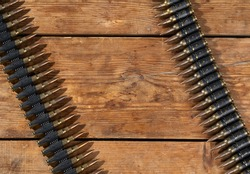 Two ammunition belts on top of a rustic wooden floor