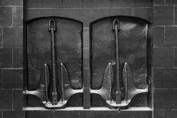 Two anchors on the wall. Black and white horizontal photo.