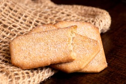 Two and half rectangular sugar coated cinnamon biscuits on hessian and dark wood table.