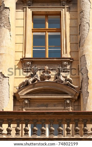 Two Angles Resting on the Facade of a Baroque Building with a Balcony and Window