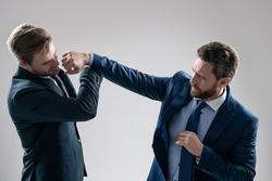 two angry businessmen punching in fight and arguing having struggle for leadership on businessmeeting because of business competition, business knockout.