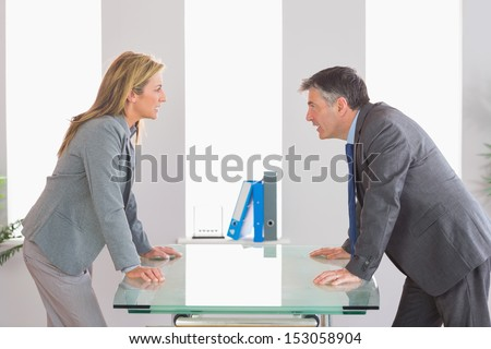 Two angry businesspeople standing arguing on each side of a desk at office