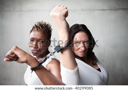 Two angry women joined by a pair of handcuffs