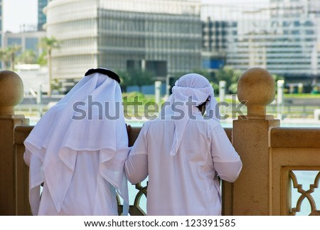 Two anonymous Arab men in traditional white clothing